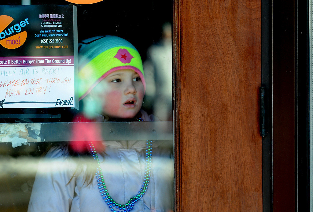 . A girl watched the Winter Carnival Grande Day Parade from inside the doorway of burger moe\'s on West Seventh Street in St. Paul, Saturday January 25, 2014.  (Pioneer Press: Jean Pieri)