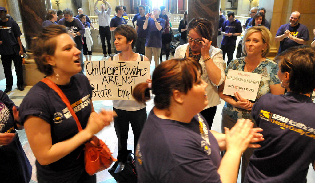 . Supporters of a bill that would allow child care providers and some personal care attendants to unionize demonstrate as three child care providers, from left, Natalie Marose, Nicki Gerrilz and Cara Benson protest the bill at the state Capitol.  (Pioneer Press: John Doman)