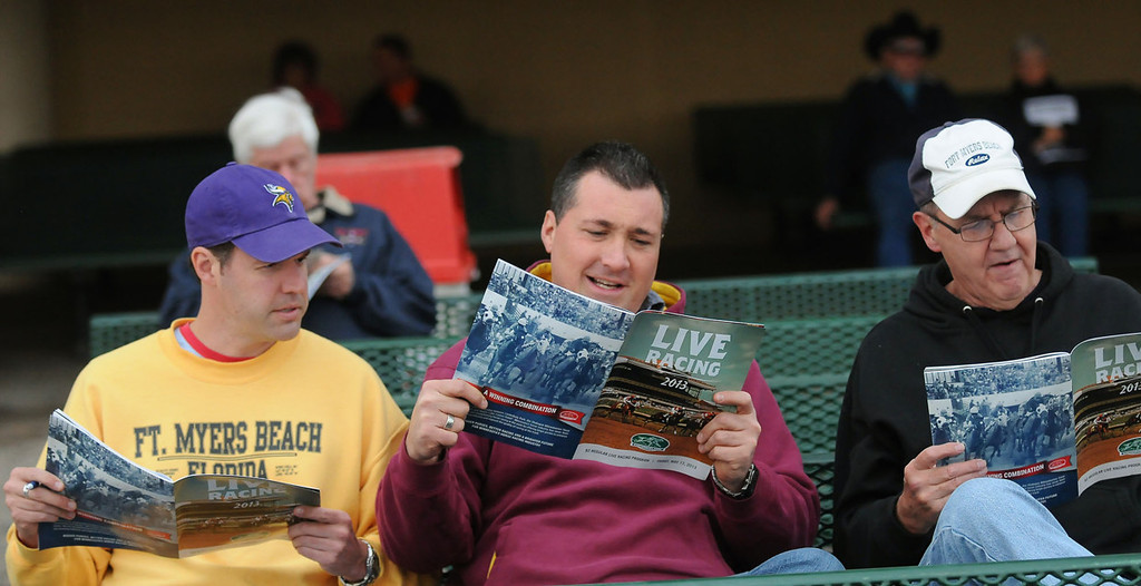 . Michael Common, left, along with his dad, Jim Common, right, and friend Aaron Gamache, center, read over the program before the start of the first race. (Pioneer Press: John Autey)