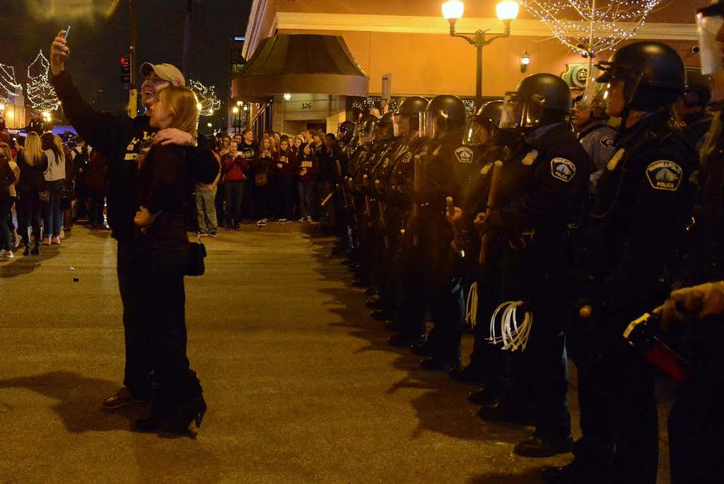 . Two people pose for a self-portrait Saturday night in front of a line of Minneapolis police. (Pioneer Press: C.J. Sinner)