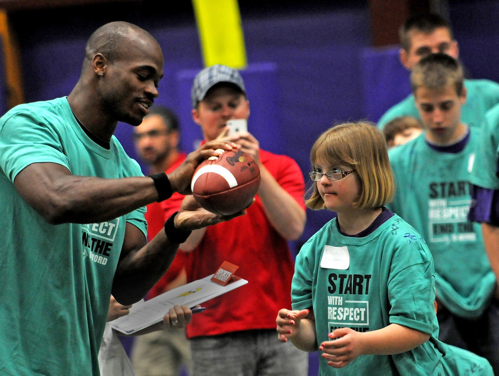 . Vikings running back Adrian Peterson, shows the proper grip on the football to a girl from the Minnesota Special Olympics before she throws. (Pioneer Press: Jean Pieri)