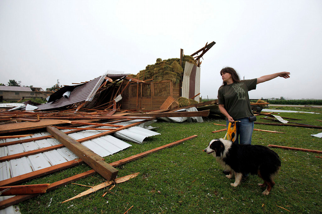 . Danielle Shaw of Greenville with her dog, Maggie, checks out damage to her horse farm on Wednesday, Aug. 7, 2013 in Hortonville, Wis. (AP Photo/The Post-Crescent, Sharon Cekada)