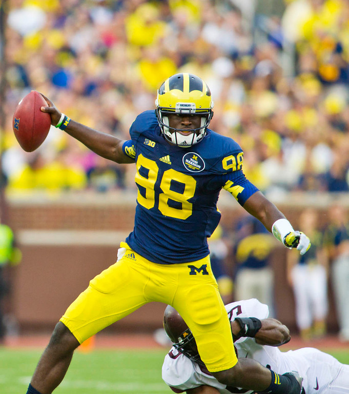 . Michigan quarterback Devin Gardner escapes a tackle from Minnesota linebacker James Manuel in the third quarter. (AP Photo/Tony Ding)