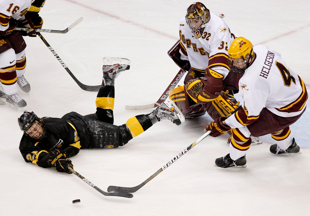 . Colorado College\'s Jeff Collett (21) fights for possession against Minnesota\'s Seth Helgeson (4) as Minnesota goalie Adam Wilcox defends during the third period of a WCHA Final Five college hockey semifinal, Friday, March 22, 2013, in St. Paul, Minn. Colorado College won 2-0. (AP Photo/Genevieve Ross)