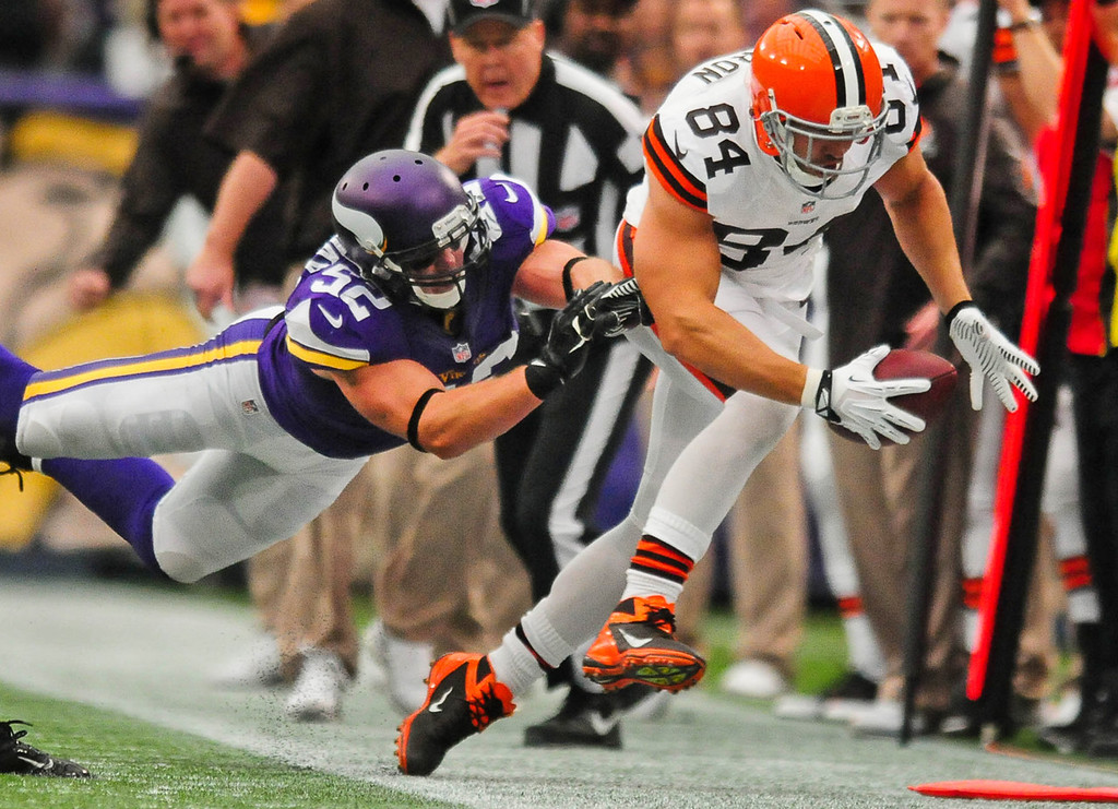 . Browns tight end Jordan Cameron, left, gets pushed out of bounds by Vikings outside linebacker Chad Greenway on an 1-yard reception in the first quarter. (Pioneer Press: Ben Garvin)