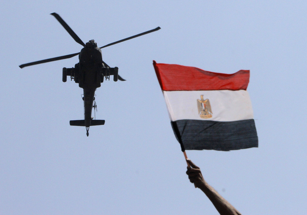 . A military helicopter flies over an opponent of Islamist President Mohammed Morsi as he waves a national flag, in Tahrir Square in Cairo, Egypt, on Tuesday, July 2, 2013. With a military deadline for intervention ticking down, protesters seeking the ouster of Egypt\'s Islamist president sought Tuesday to push the embattled leader further toward the edge with another massive display of people power. (Associated Press: Amr Nabil)
