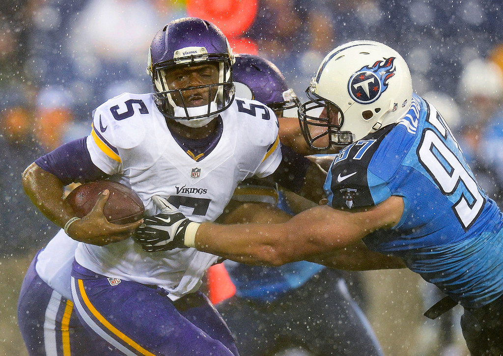 . Minnesota Vikings quarterback Teddy Bridgewater breaks away from the grasp of Tennessee Titans defensive end Karl Klug in the rain during the first quarter. (AP Photo/Mark Zaleski)