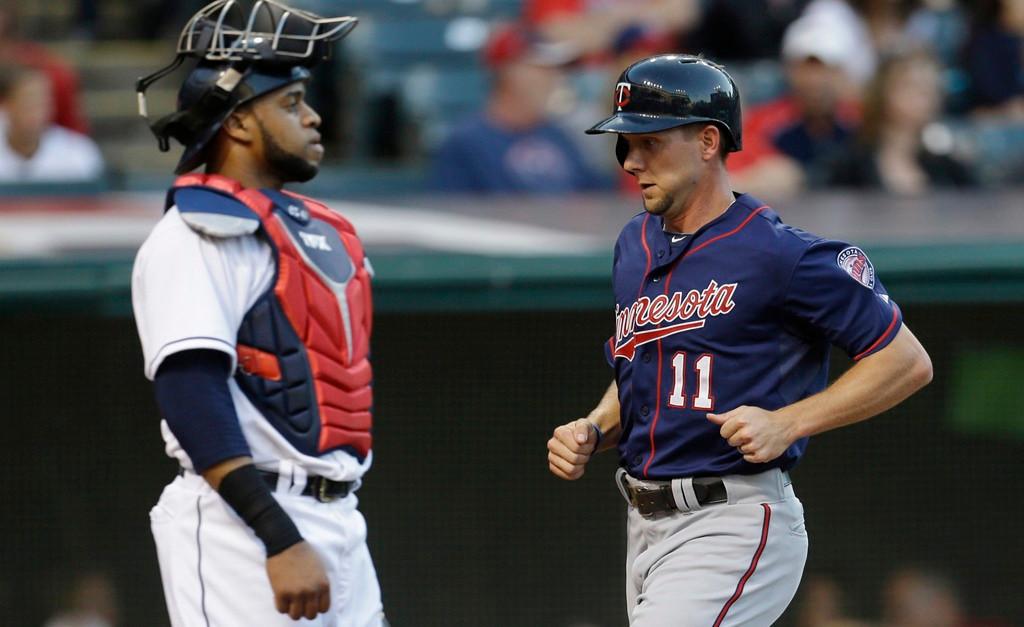 . Minnesota\'s Clete Thomas, right, passes Indians catcher Carlos Santana as he scores on a Pedro Florimon double in the second inning. (AP Photo/Tony Dejak)