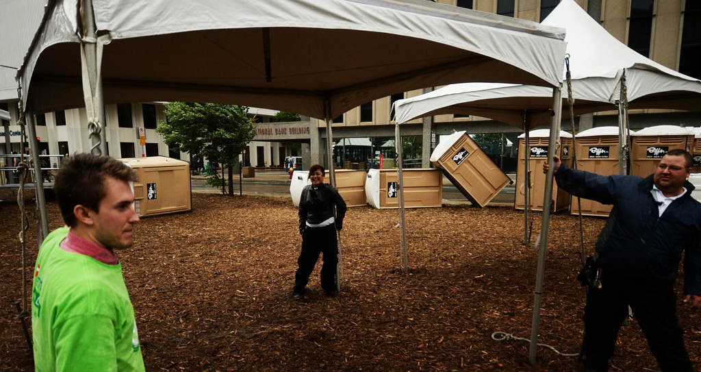 . Security guards and volunteers hold tents to the ground against high winds behind the Central Station in downtown St. Paul. Several portable restrooms lay blown over by the wind behind the trio.  (Pioneer Press: John Autey)