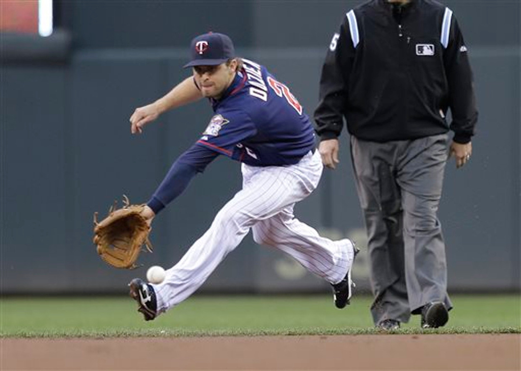 . Minnesota Twins\' Brian Dozier fields a grounder for a single by Boston Red Sox\' Daniel Nava in the first inning. Nava advanced to second on a throwing error by Dozier on the play. (AP Photo/Jim Mone)