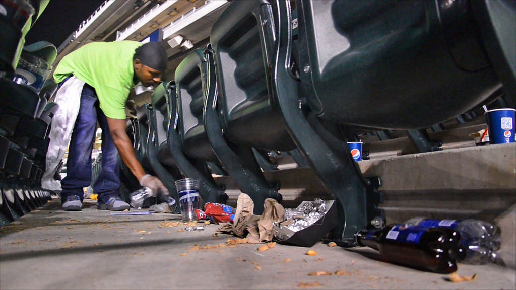 . A member of the cleaning crew scoops up leftover refuse in the stands after a game against the Yankees. (Pioneer Press: John Autey)