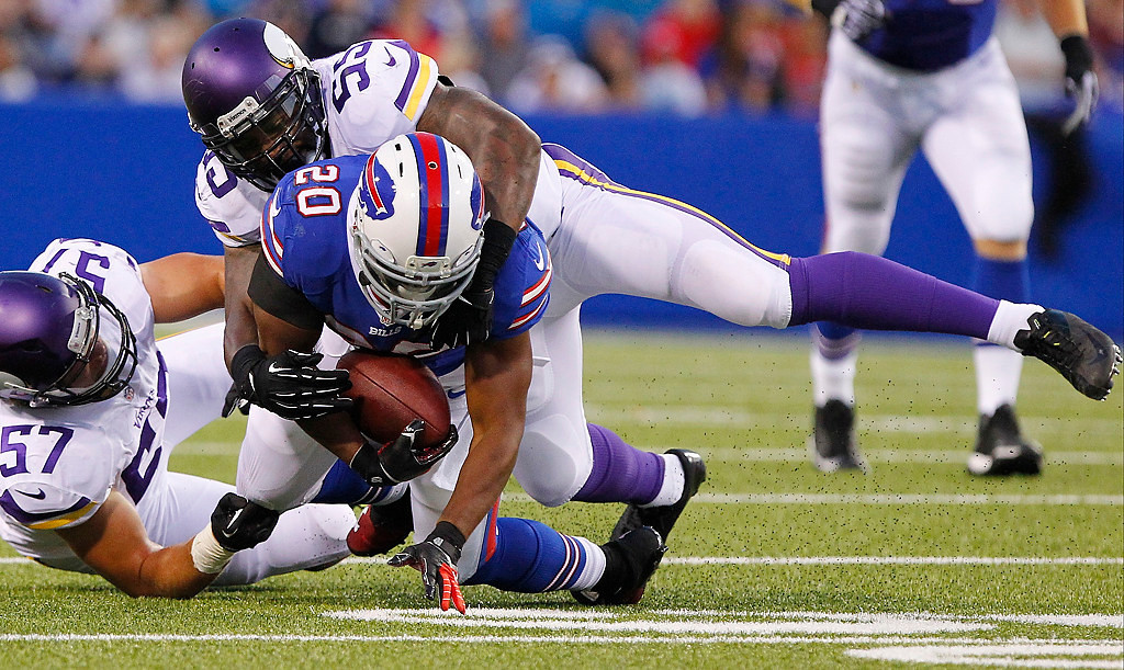 . Buffalo Bills\' Tashard Choice (20) is tackled by Minnesota Vikings\' Audie Cole (57) and Desmond Bishop (55) during the first half of an NFL preseason football game Friday, Aug. 16, 2013, in Orchard Park, N.Y.  (AP Photo/Bill Wippert)