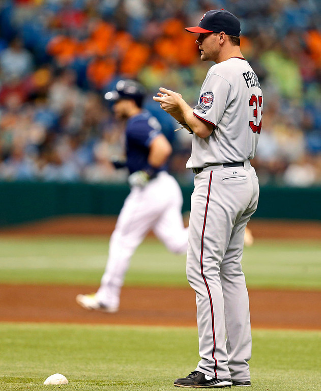. Twins starter Mike Pelfrey reacts after giving up a solo home run to Tampa Bay\'s Luke Scott, rounding the bases in the background, during the sixth inning. (AP Photo/Mike Carlson)
