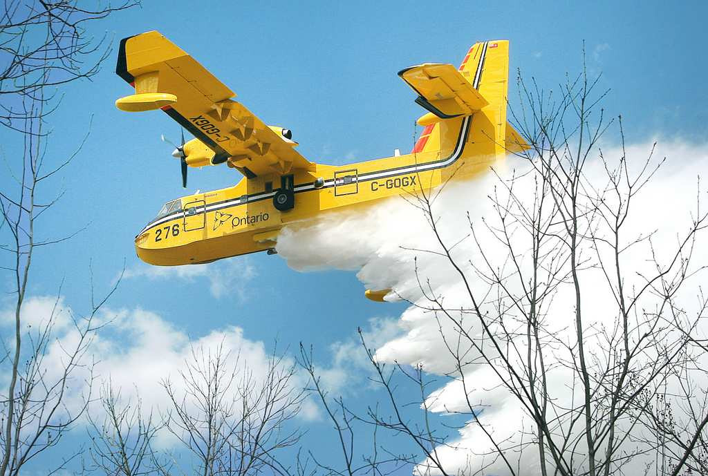 . A Bombardier 415 water bomber operating out Ontario dumps a load water on a fire along East Beauregard Lake Road on Wednesday afternoon, May 15, 2013, near Barnes, Wis. Authorities are investigating whether logging operations may have sparked a massive wildfire in northwestern Wisconsin that destroyed dozens of buildings and forced at least 60 people to evacuate, state officials said. (Associated Press/Duluth News-Tribune: Bob King)