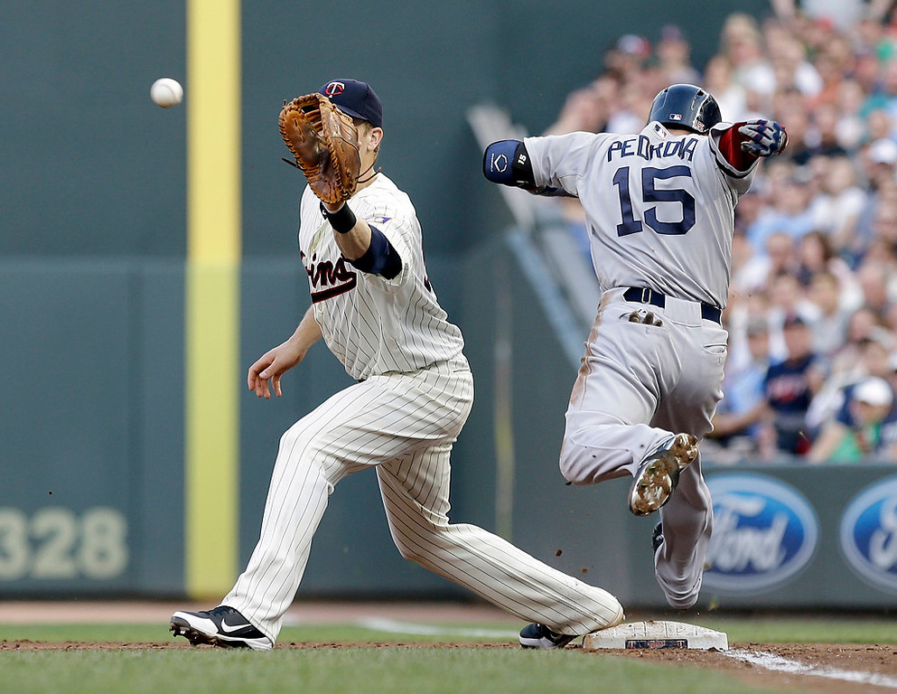 . Boston\'s Dustin Pedroia beats the throw to Minnesota Twins first baseman Justin Morneau for a single in the third inning. (AP Photo/Jim Mone)