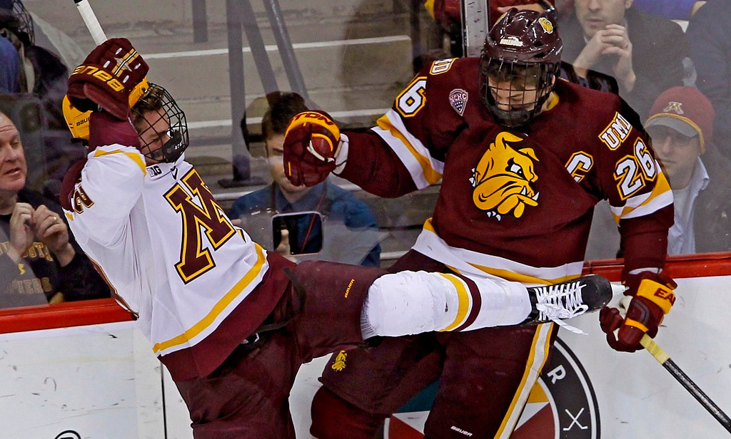 . Minnesota Duluth right wing Adam Krause, right, checks Minnesota right wing Christian Isackson off the puck during the first period. (AP Photo/Ann Heisenfelt)