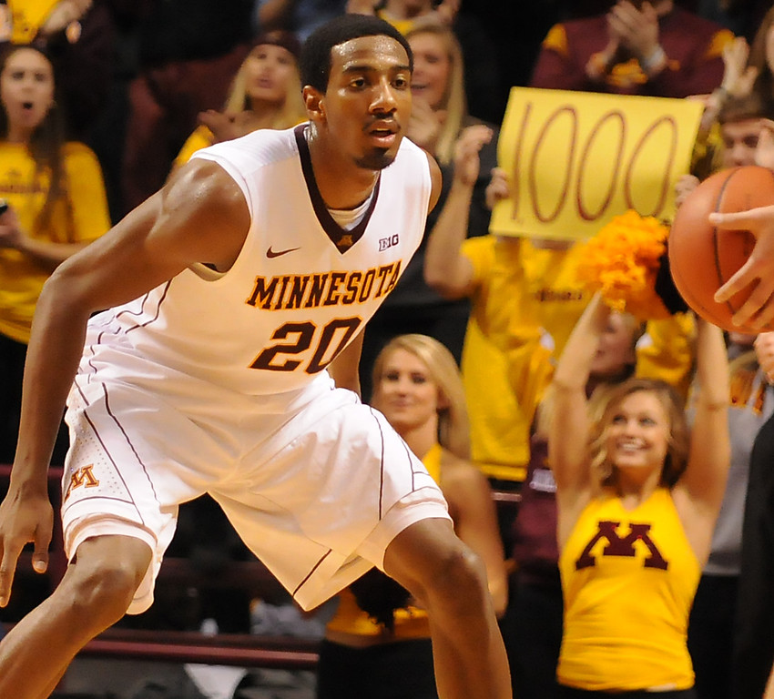 . Minnesota guard Austin Hollins defends against South Dakota State as fans hold up a sign celebrating his 1000th point.(Pioneer Press: John Autey)