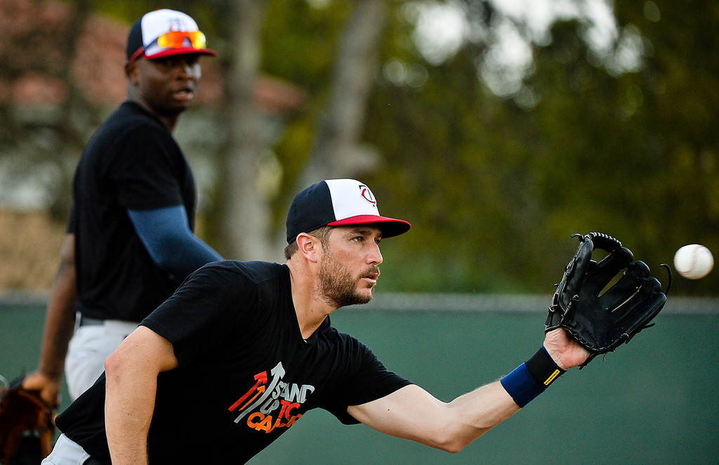 """. Twins third baseman Trevor Plouffe catches the ball as Miguel Sano watches during Kelly\'s famous \""""Good Morning America\"""" drill. (Pioneer Press: Ben Garvin)"""