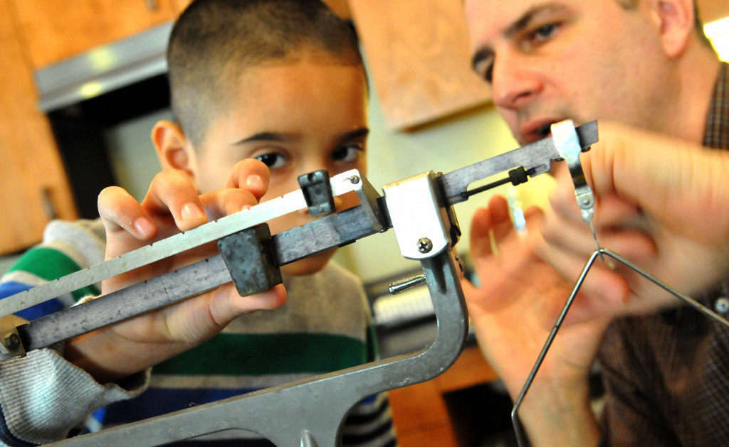 . With the help from Lower Elementary teacher John Albright, right, Joel Tristan-Lopez is taught the concept of measuring weight. Charters and traditional public schools in St Paul have organized their first Small Schools Week. Cornerstone Montessori School on St. Paul\'s East Side is  a charter school organized in 2011.  (Pioneer Press: John Doman)