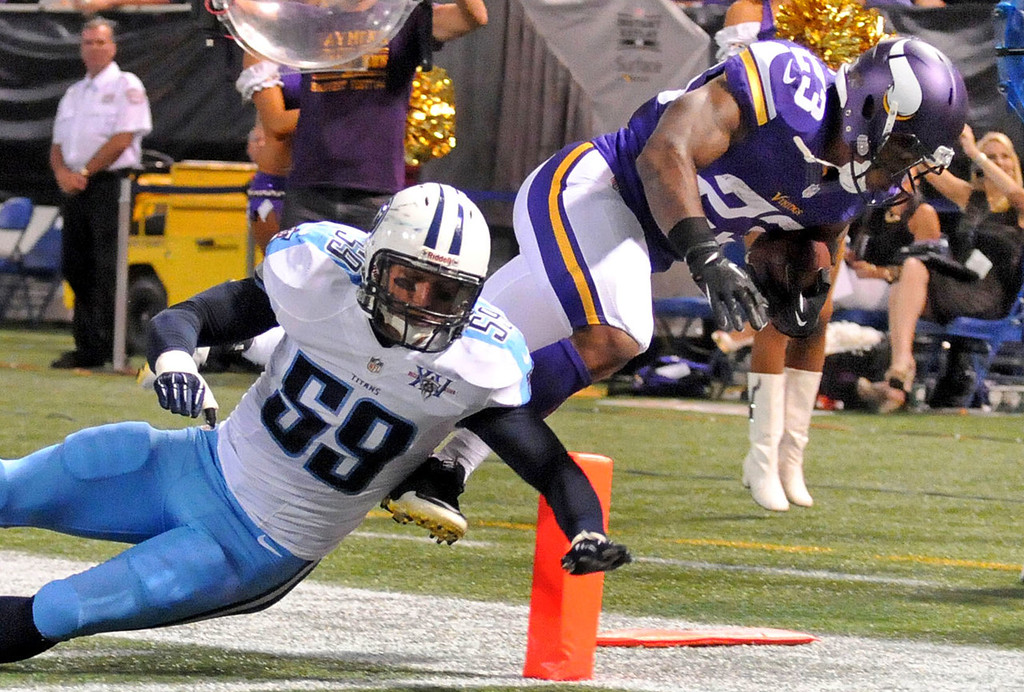 . Vikings running back Joe Banyard, right, leaps over Titans middle linebacker Tim Shaw to score on an 11-yard pass play during the second quarter.  (Pioneer Press: Sherri LaRose-Chiglo)
