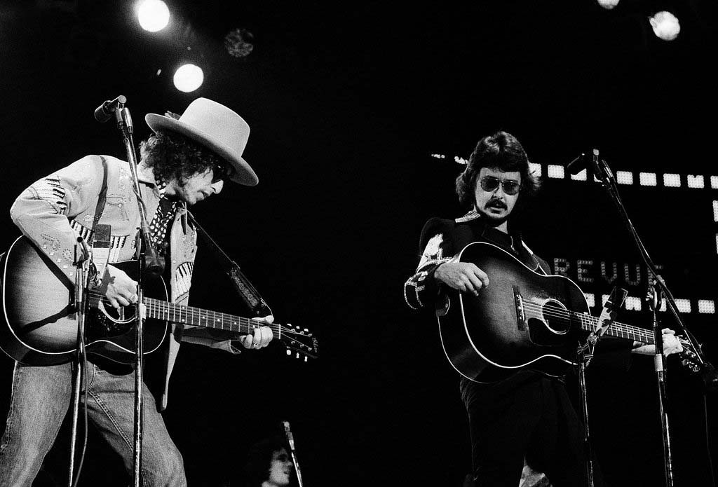 """. 1976: Dylan singing at a benefit concert for Rubin \""""Hurricane\"""" Carter with Bob Neuwirth, January 1976. (AP Photo)"""