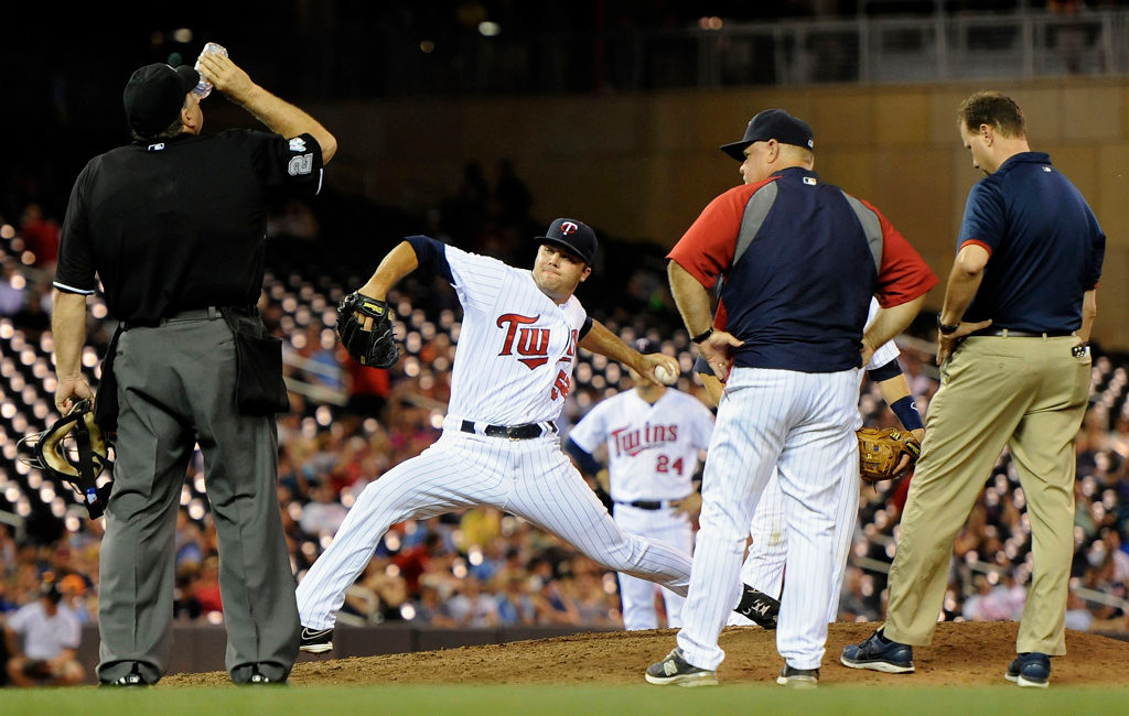 . Caleb Thielbar #56 of the Minnesota Twins delivers a pitch after a potential injury as home plate umpire Jerry Layne #24, manager Ron Gardenhire #35 and trainer Lanning Tucker look on during the eighth inning. (Photo by Hannah Foslien/Getty Images)