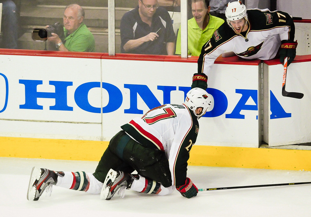 . Minnesota Wild left wing Mike Rupp crawls back to the bench as he\'s cheered on by Torrey Mitchell, top, after Rupp lost one of the metal blades in his skates in overtime. (Pioneer Press: Ben Garvin)