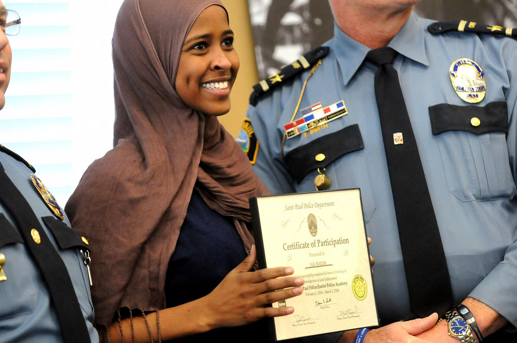 . Yuki Abdulle, 19, smiles as she receives her certificate of participation from Chief of Police Thomas Smith, right, and Assistand Chief Todd Axtell, left, during a graduation ceremony on Saturday, March 1, 2014, for the East African Junior Police Academy at the Western District Police Station in St. Paul. (Pioneer Press: Sherri LaRose-Chiglo)