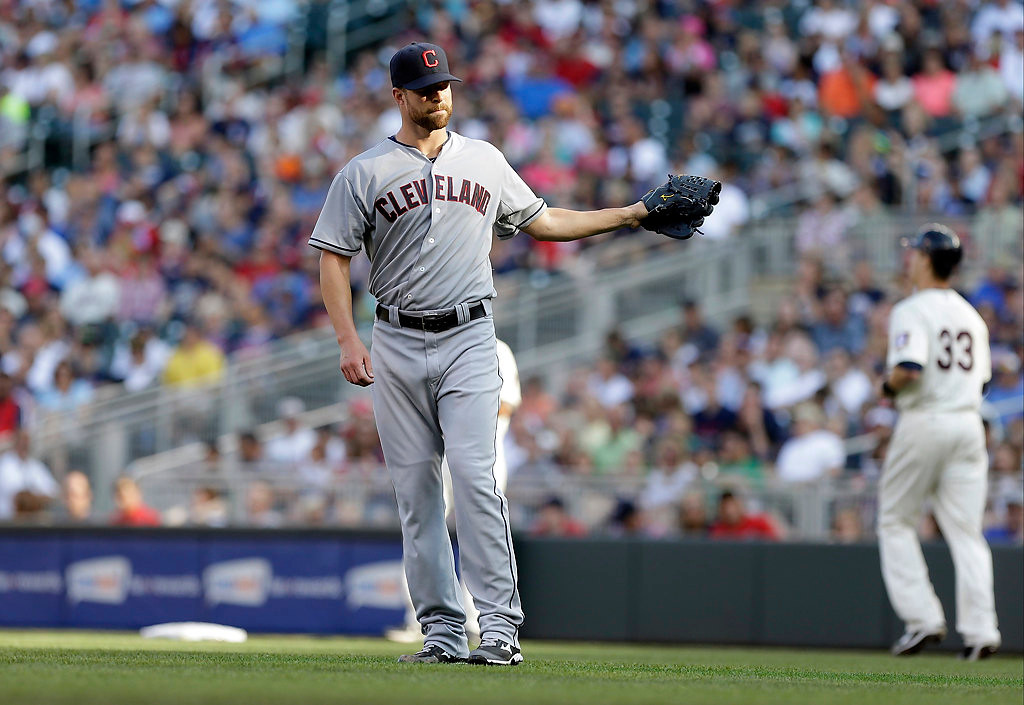 . Cleveland Indians pitcher Corey Kluber, left, gives up a walk to Minnesota Twins\' Justin Morneau, right, in the first inning. (AP Photo/Jim Mone)