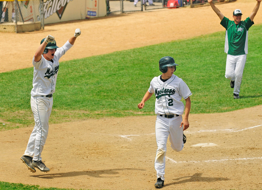 . Mounds View\'s Chance Carnaha, pinch running for teammate Charlie Callahan, crosses home plate with the winning run in the bottom of the seventh inning, driven in by Alec Abercrombie\'s single, to give the Mustangs a 2-1 quarterfinal win over Forest Lake. Cheering the win at left is Mounds View\'s  Mitch Fredrickson.   (Pioneer Press: Scott Takushi)