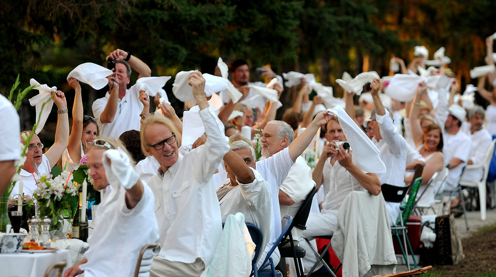 """. White-clad diners signal for the start of their supper. The event is modeled after \""""Diner en Blanc,\"""" a 25-year tradition in France. (Pioneer Press: Sherri LaRose-Chiglo)"""