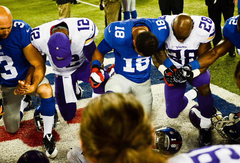 . Vikings quarterback Josh Freeman, left, and running back Adrian Peterson pray after teh game with Giants wide receiver Louis Murphy, center. (Pioneer Press: Ben Garvin)