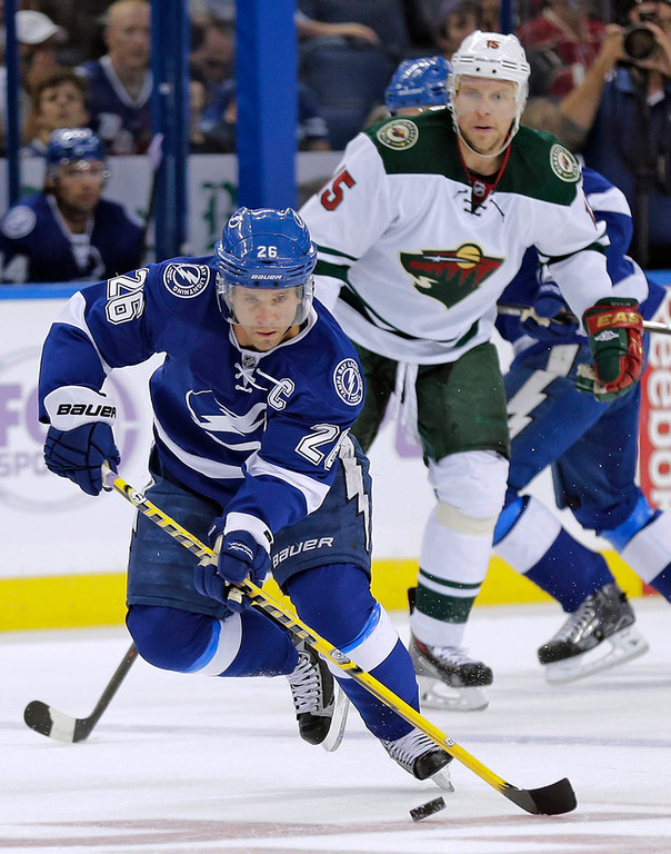 . Tampa Bay Lightning right wing Martin St. Louis (26) carries the puck around Minnesota Wild right wing Dany Heatley (15) during the first period.  (AP Photo/Chris O\'Meara)