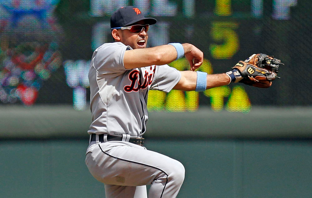 . Tigers second baseman Omar Infante makes the throw to first base for an out on a grounder by Twins batter Ryan Doumit during the ninth inning. (AP Photo/Genevieve Ross)