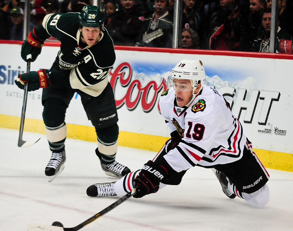. Chicago center Jonathan Toews, right, takes a diving shot on goal as he\'s covered by Minnesota defenseman Ryan Suter in the first period.