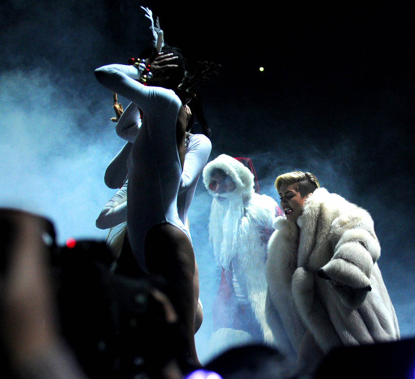 . Miley Cyrus walks on stage with a Santa as her reindeer dancers are at left at Xcel Energy Center in St. Paul, Tuesday, December 10, 2013. (Pioneer Press: Chris Polydoroff)