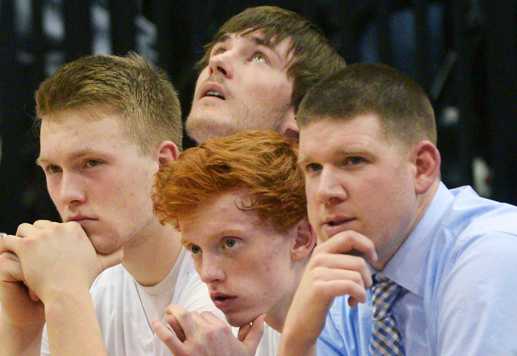 . St. Francis junior center Blake Moreno, left, senior forward Mitch Wenker (looking up), senior guard Cody Wald and assistant coach Matt Norton look on in the final moments of their 69-53 loss to the Raiders. (Pioneer Press: John Autey