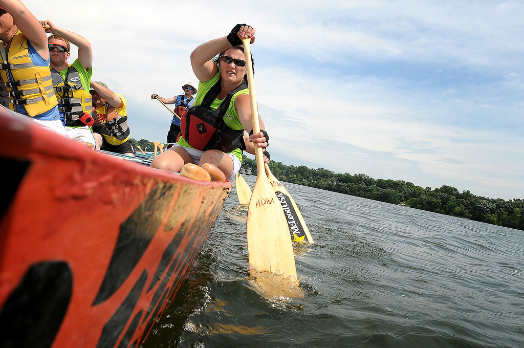 . Kris Miller and fellow volunteers paddle back from a pontoon boat at the start of the race during the team practice time on Lake Phalen at the 10th annual Dragon Festival at Phalen Park in St. Paul on Sunday, July 14, 2013. (Pioneer Press: Sherri LaRose-Chiglo)