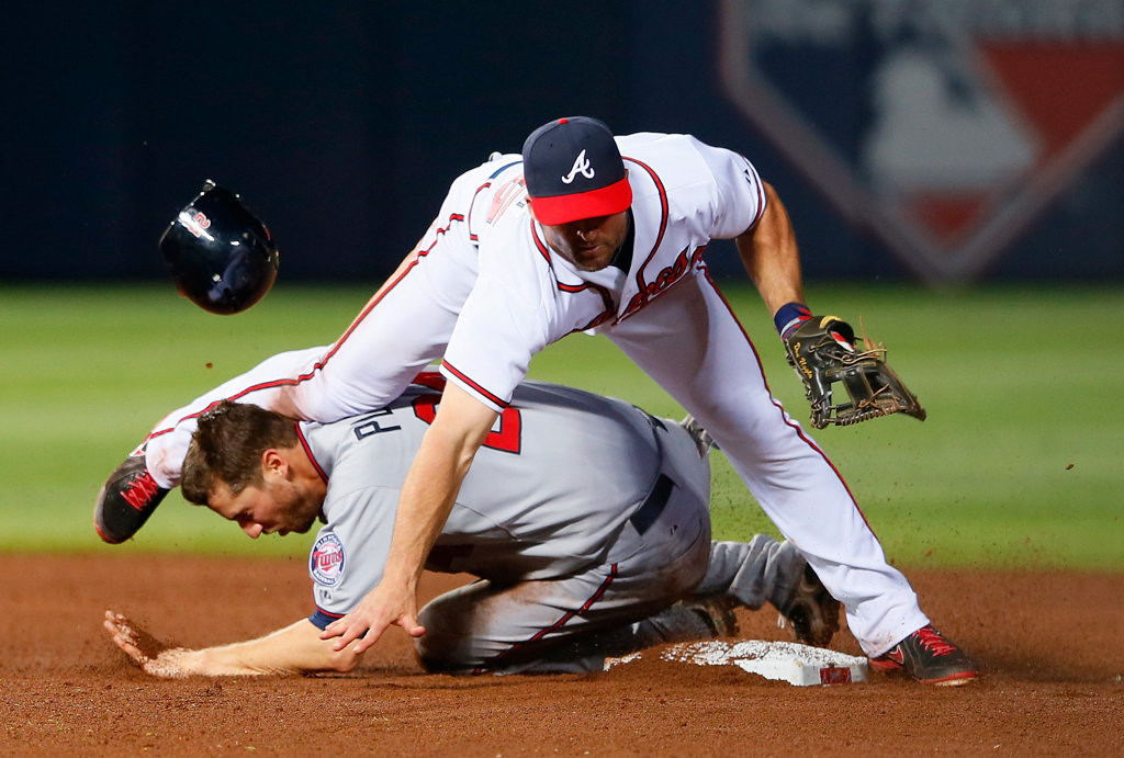 . Dan Uggla of the Atlanta Braves attempts a double play ball as knee slams into the head of a sliding Trevor Plouffe #24 of the Minnesota Twins in the 10th inning.  (Photo by Kevin C. Cox/Getty Images)