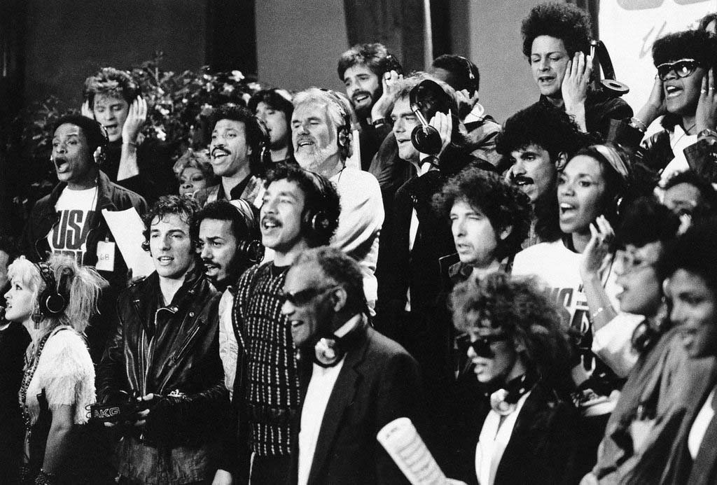 """. Some of a group of 45 music artists calling themselves \""""USA For Africa\"""" recording \""""We Are The World\"""" in Los Angeles, Calif.  Jan. 30, 1985. Bottom row, from left; Cyndi Lauper, Bruce Springsteen, James Ingram, Smokey Robinson, Ray Charles, Sheila E., June Pointer, Randy Jackson. Middle row, from left; Al Jarreau, Dionne Warwick, Lionel Richie, Kenny Rogers, Huey Lewis, Bob Dylan, John Oates, Ruth Pointer. Top row, from left; Daryl Hall, Steve Perry, Kenny Loggins, Jeffrey Osborne, Lindsay Buckingham, and Anita Pointer.  (AP Photo)"""