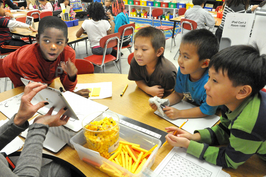 . Third graders (from left) Maurice White, Nicholas Pha, Tom Chang and David Hong work on adding double digit numbers with their teacher, Tara Kuehlwein, at Frost Lake Elementary. (Pioneer Press: John Doman)