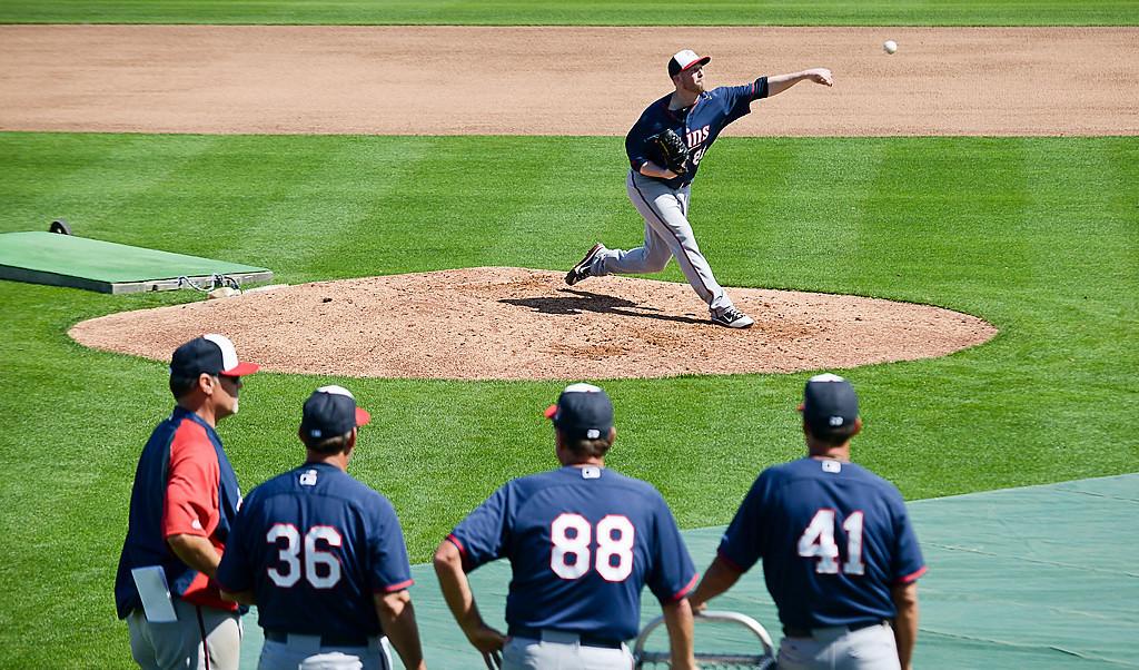 . Coaches watch as non-roster invitee Matt Hoffman delivers during live batting practice. (Pioneer Press: Ben Garvin)