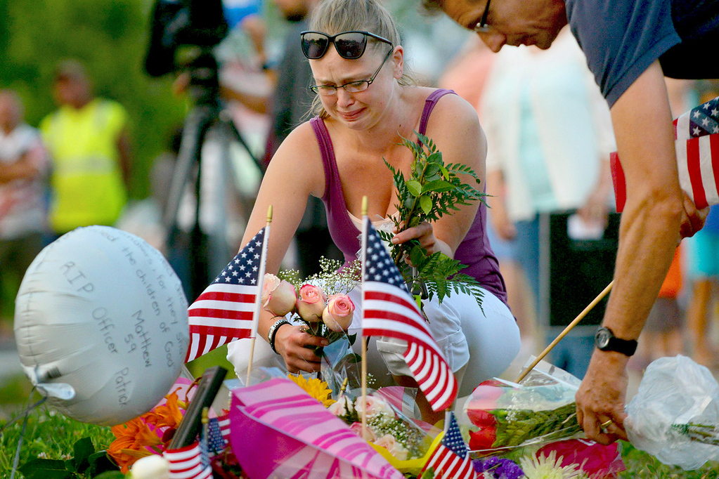 . Gail Krull of West St. Paul, a niece of Mendota Heights Police Officer Scott Patrick, cries as she lays a bouquet of roses on a makeshift memorial during a candle light vigil at the location where Patrick was shot and killed in West St. Paul on Wednesday, July 20, 2014. Officer Patrick was killed while performing a traffic stop on Dodd Road near Smith Avenue earlier on Wednesday. (Pioneer Press: John Autey)