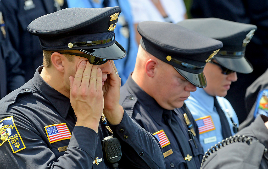 . Robbinsdale police officer Alex Weber cries outside St. Stephen\'s Lutheran Church in West St. Paul during the funeral service for fallen Mendota Heights officer Scott Patrick on Wednesday. (Pioneer Press: Ben Garvin)