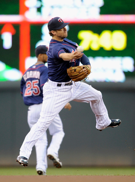 . Brian Dozier overthrows to first baseman Justin Morneau during the first inning.  (Photo by Hannah Foslien/Getty Images)