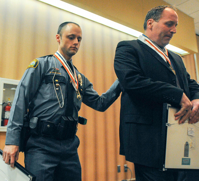 . St. Paul Police officer Brian Wanschura, left, exits the podium with his partner, Dan King, after the pair were honored as Officers of the Year, and also received the Medal of Valor.  (Pioneer Press: Chris Polydoroff)