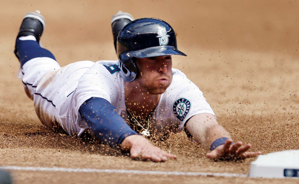 . Seattle\'s Brad Miller dives safely into third in the third inning on a single by teammate Nick Franklin against the Twins. (AP Photo/Elaine Thompson)