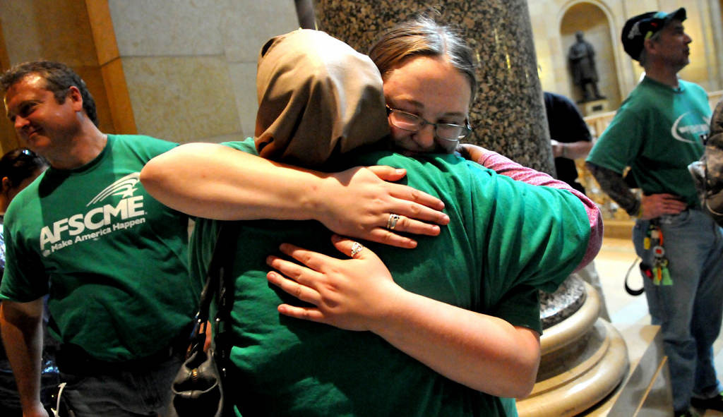 . Child care worker Hawo Gurney of Minneapolis, front, is hugged by AFSCME organizer Coly Wentzlaff after the child care unionization vote came in in their favor Monday. The Minnesota House passed a bill that allows a union drive among home day care providers and personal care attendants after about 10 hours of debate strung out over more than two days.  (Pioneer Press: John Doman)
