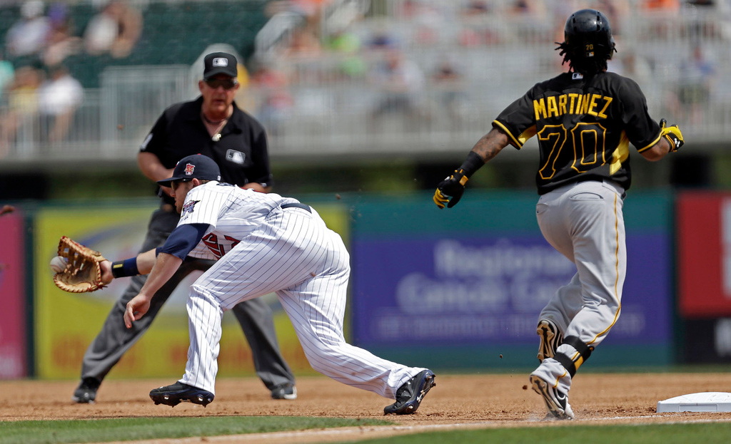 . Twins first baseman Chris Parmelee fields as Pirates shortstop Michael Martinez reaches first on a bunt single in the first inning. (AP Photo/Gerald Herbert)