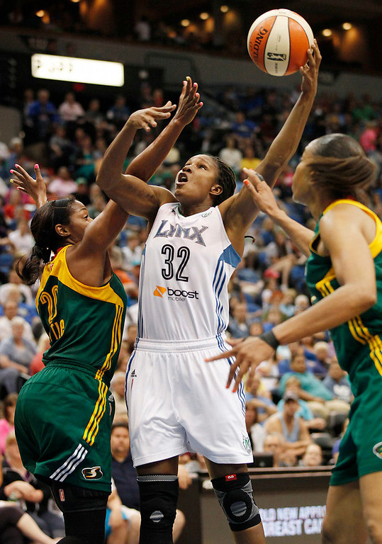 . Minnesota Lynx forward Rebekkah Brunson (32) goes up to the basket against Seattle Storm forward Camille Little (20) and forward Tina Thompson (7) in the first half of a WNBA basketball game, Sunday, Aug. 4, 2013, in Minneapolis. (AP Photo/Stacy Bengs)